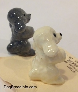 The right side of figurines of a Poodle puppy in a begging pose. The Figurines have big black circles for eyes.