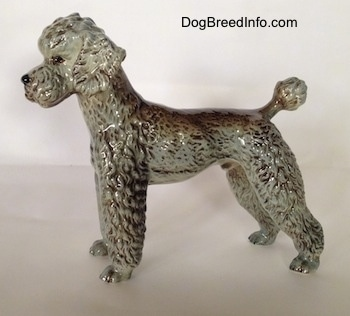 The right side of a black, gray and brown Poodle figurine. The figurine has a poof at the end of its small tail.