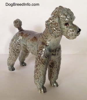 The front right side of a black, gray and brown figurine of a Poodle. The figurine has tiny paws.