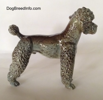 The right side of a figurine of a black, gray and brown Poodle. The body of the poodle is average length.