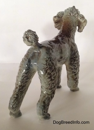 The back right side of a black, gray and brown Poodle figurine. The figurine has fine hair details.