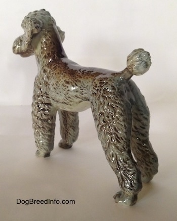 The back left side of a black, gray and brown figurine of a Poodle standing.