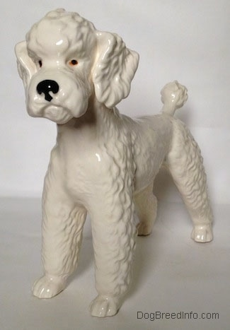 The front left side of a figurine of a white Poodle. The eyes of the figurine are black and orange.