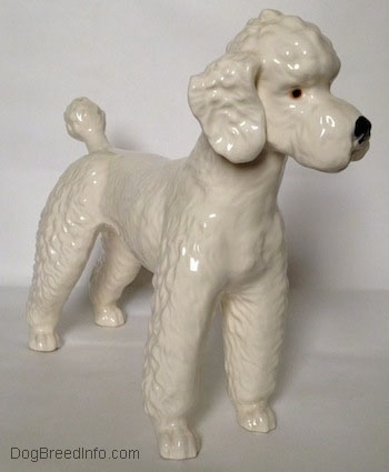 The front right side of a white Poodle figurine. The figurine has detailed hairy legs.