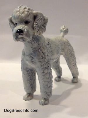 White with a blue tint vintage West Germany porcelain Standard Poodle dog figurine by Goebel. Front-side view