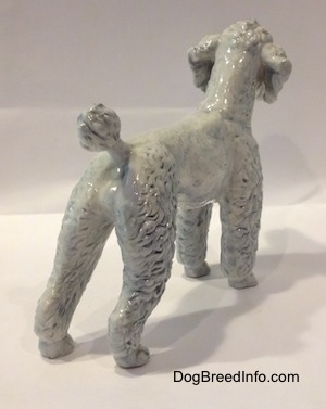 The back right side of a figurine of a porcelain white with blue Poodle. The figurine has a short poofy tail.