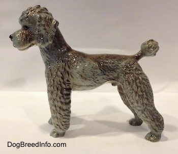 The left side of a black, gray and brown Poodle standing figurine. The figurien is glossy.
