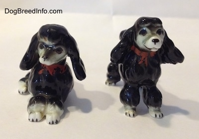 Two black with white bone china Poodle figurines. One figurine is lying down and the other is standing.