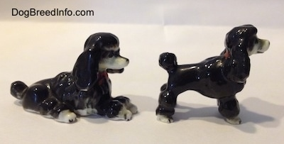 The right side of two black with white bone china figurines of Poodles. Both figurines have short hair poofy tails.