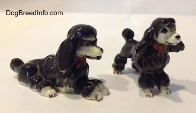 The front right side of two bone china figurines of black with white Poodles. The figurines are wearing red bowtie collars.
