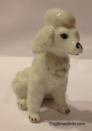 A white bone china Poodle figurine that is in a sitting position. The figurine has black tipped nails.
