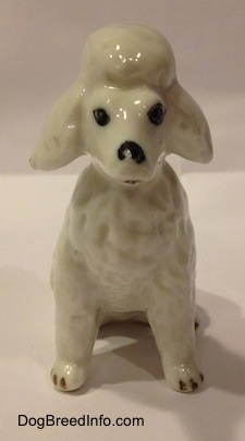 A white Poodle figurine that is in a seated position. The figurine has a mouth that is painted slightly open.