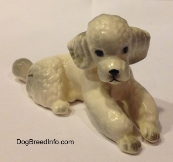 A white ceramic Poodle figurine that is in a lying position. The figurine has black circles for eyes.