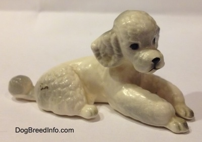 The front right side of a ceramic figurine of a white Poodle that is in a lying position. The figurine has poofy legs.