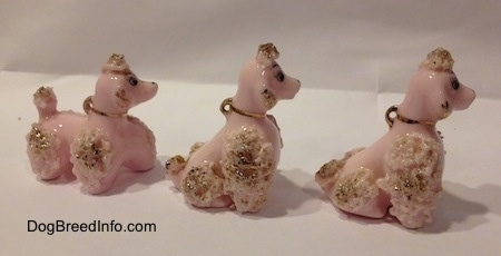 The right side of three figurines of a pink spaghetti Poodle puppy. Two of the figurines are in a sitting position.