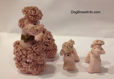 Vintage pink spaghetti Poodle porcelain set figurines from the 1940s to 1950s.