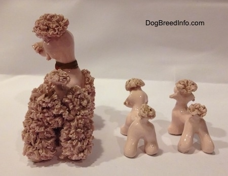 The back of three porcelain pink spaghetti figurines. The tails of the figurines have rough bristles for tails and on top of there heads.