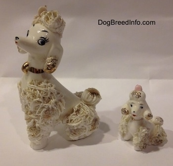 The front left side of two porcelain white spaghetti figurines. The Adult figurine has very detailed eyes. The puppy figurine has black circles for eyes.
