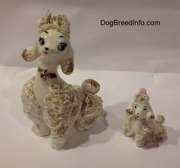 Two white spaghetti Poodle porcelain figurines that are in sitting positions. The bottoms of there ears are gold.