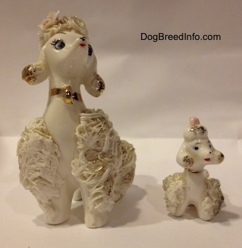 Two white Spaghetti porcelain figurines of Poodles. The figurines have there mouths painted open.
