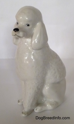 The front left side of a figurine of a porcelain white standard Poodle in a sitting pose. The figurine has long legs.