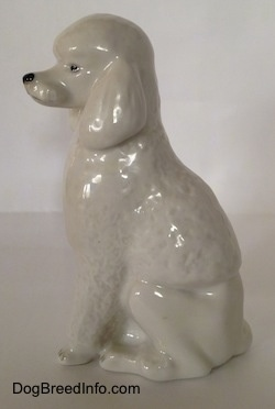 The left side of a porcelain white standard Poodle figurine in a sitting pose. The figurine has very fine hair details along its body and front legs.