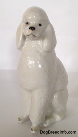 The front right side of a white standard Poodle sitting porcelain figurine. The figurine has black circle for eyes.