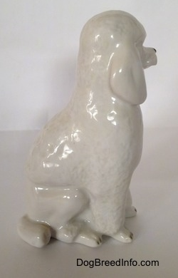 The right side of a white porcelain standard Poodle in a sitting pose figurine. The figurine has a tail along the side of its legs.