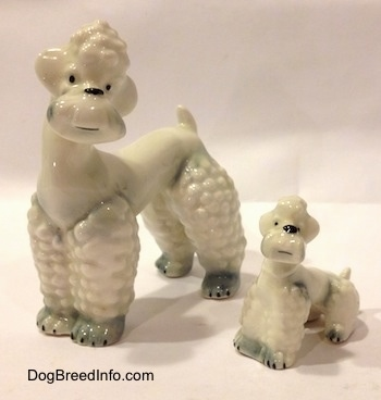 The front left side of two white with spots of gray Poodle figurines. The figurines have small black eye dots.