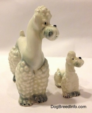 The front right side of two white spots of gray figurines of Poodles. The figurines hace black circles for noses.