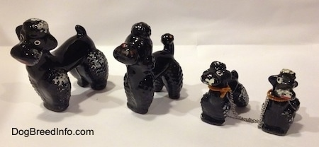The front left side of four black clay Poodle figurines. Three of the figurines are chipped.