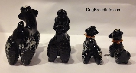 The back of four black clay figurines of Poodles. The figurines have short tails that are arched in the air.