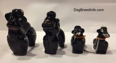 Four black clay Poodle figurines. Two of the figurines are adult and two are adults. Each figurine has a poof of hair on therehead.