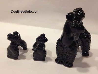 There are three black Poodle figurines. Two puppy figurines and an adult one. The figurines are glossy/