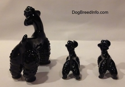 The back of three black Poodle figurines. The figurines have lumpy legs.