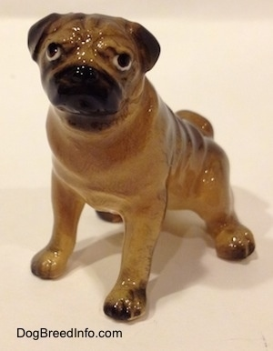 The front left side of a miniature Pug seated figurine.The figurine has short legs and small paws.