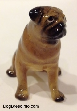 A brown with black miniature Pug figurine that is seated. The figurine has black ears.