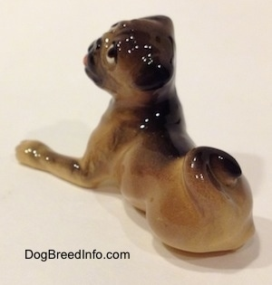 The back left side of a figurine of a brown with black miniature Pug lying down. The figurine has its tail swirled onto its back.