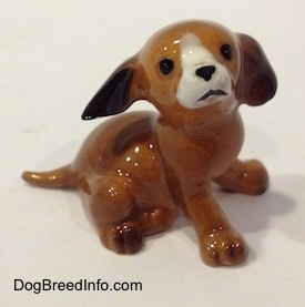The right side of a brown with white mini puppy sitting figurine. The figurine has black circles for eyes.