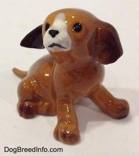 The front right side of a miniature puppy sitting figurine. The figurine is glossy.