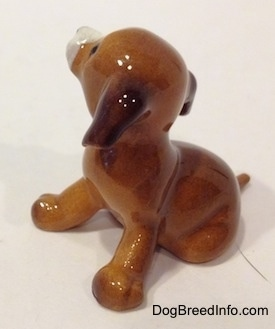 The left side of a figurine of a brown with white miniature puppy sitting figurine. The figurine has long ears.