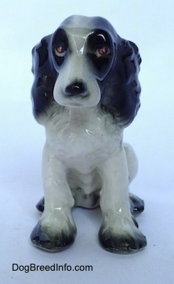 A black with white Russian Spaniel dog figurine in a sitting pose. The figurine has red eyes.