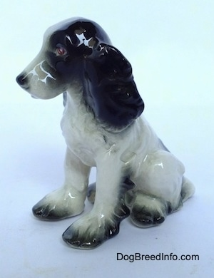 The front left side of a Russian Spaniel sitting figurine. The ears of the figurine are bumpy and black.