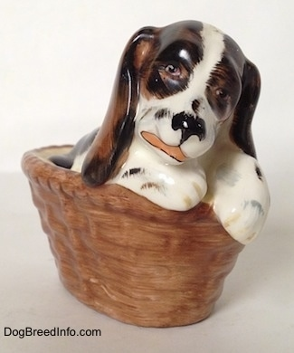 A white with brown and black figurine of a Russian Spaniel puppy in a basket. The figurine has detailed eyes.
