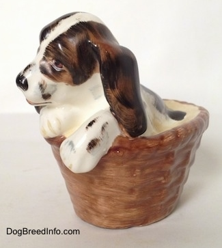 The front left side of a white with brown and black Russian Spaniel puppy in a basket figurine. The figurine has its paws on the edge of the basket.