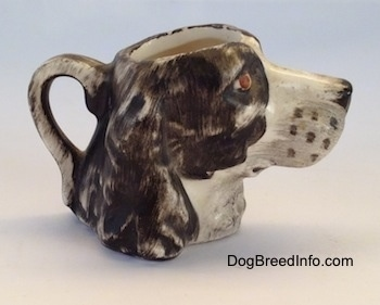 The right side of a brown and white Russian Spaniel dog stein cup. The ears are hard to see against the head of the cup.
