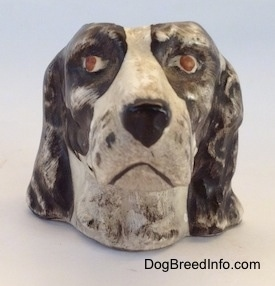 A brown and white Russian Spaniel dog stein cup. The figurine has red eyes.
