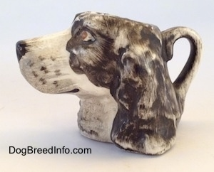 The left side of a stein cup that is of a brown and white Russian Spaniel dog. The handle of the stein is painted like the ears of the figurine.