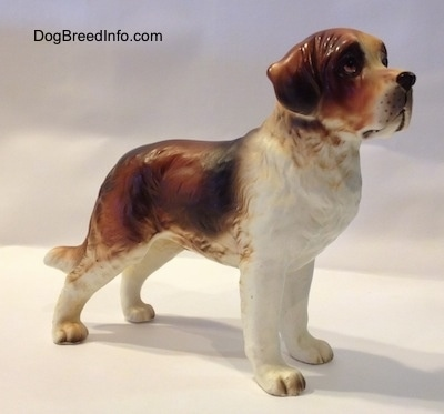 The front right side of a figurine of a Saint Bernard. The figurine has long legs.