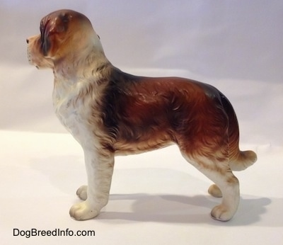 The left side of a brown and white figurine of a Saint Bernard. The figurine has fine hair details.